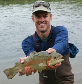 Daniel Vimont holding a rainbow trout while standing in Big Green River